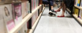Image of two people touching feet in a library